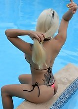 Sexy Blonde TRANNY hides her package in a Thong Bikini at the Pool